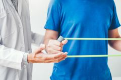 Physiotherapist man giving resistance band exercise treatment About Chest muscles and Shoulder of athlete male patient Physical. Physiotherapist men giving royalty free stock image