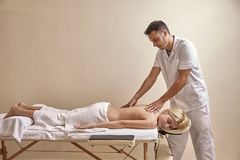 Free Physiotherapist Massage, Woman Back Laying On Bed. Full Lenght Shot. Stock Photography - 129737212