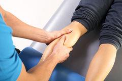 Physiotherapist massaged patient's leg. Royalty Free Stock Image