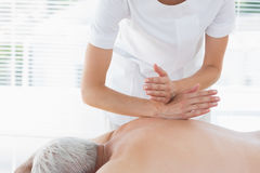 Physiotherapist massaging back of man Royalty Free Stock Image