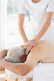 Physiotherapist massaging back of patient Stock Photos