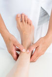 Physiotherapist massaging her patients ankle Royalty Free Stock Photography