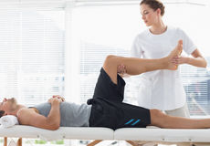 Physiotherapist massaging leg of man Stock Photos