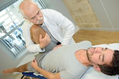 Physiotherapist massaging leg patient in physio room Stock Photos