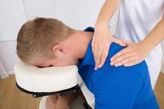 Physiotherapist massaging man's shoulder Stock Photos