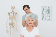 Physiotherapist massaging a senior womans neck Stock Images