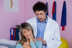 Physiotherapist massaging a senior womans shoulder Stock Photography