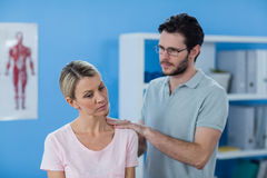 Physiotherapist massaging shoulder of a female patient Royalty Free Stock Photo