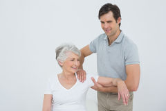 Physiotherapist massaging a smiling senior womans arm Stock Photos