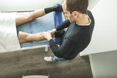 Physiotherapist masuje młody człowiek łydki Fizjoterapia i rehabilitacja obraz stock
