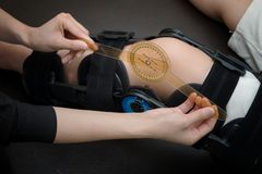 Physiotherapist measuring range of motion on patients` knee with Stock Image
