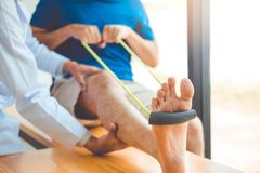 Physiotherapist man giving resistance band exercise treatment About knee of athlete male patient Physical therapy concept. Physiotherapist men giving resistance stock photo
