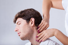 Physiotherapist palpationing patient with stiff neck. Closeup of physiotherapist palpationing patient with stiff neck Stock Images