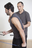 Physiotherapist with patient. Physiotherapist helping patient holding his back Royalty Free Stock Images