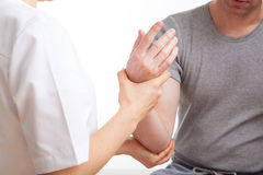 Physiotherapist with patient. Patient with elbow ache has rehabilitation in physiotherapy clinic Royalty Free Stock Image