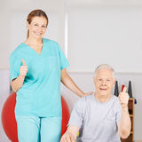 Physiotherapist and patient holding thumbs up Royalty Free Stock Photos
