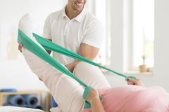 Physiotherapist performing exercises with patient Royalty Free Stock Photos
