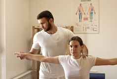 Physiotherapist practicing with patient. Young male Physiotherapist training with patient. hand exercise. White uniforms Stock Images