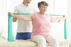 Physiotherapist providing help. With easing the pain of joints through pnf exercises involving a scarf for his elderly patient Stock Image