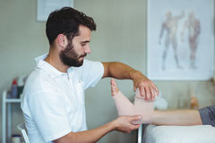 Physiotherapist putting bandage on injured feet of patient Royalty Free Stock Images