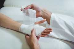 Physiotherapist putting bandage on injured hand of patient Stock Image