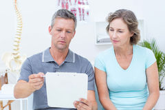 Physiotherapist reading his notes with his patient Stock Photos
