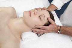 Physiotherapist relieving migraines Stock Image