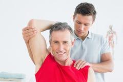 Physiotherapist rozciąga uśmiechnięty dojrzałego obsługuje rękę Obraz Royalty Free