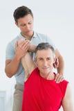 Physiotherapist rozciąga uśmiechnięty dojrzałego obsługuje rękę Obrazy Royalty Free