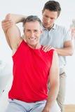 Physiotherapist rozciąga uśmiechnięty dojrzałego obsługuje rękę Fotografia Royalty Free