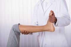 Physiotherapist Giving Leg Exercise To Patient. Physiotherapist`s Hand Giving Leg Exercise To Female Patient In Clinic royalty free stock images