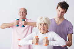 Physiotherapist and seniors. Physiotherapist helping active seniors in exercises stock photos