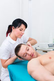 Physiotherapist set patient in practice Royalty Free Stock Images