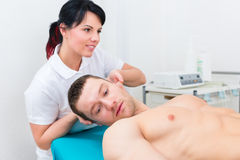 Physiotherapist set patient in practice Royalty Free Stock Photos