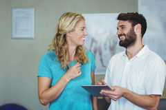 Physiotherapist showing digital tablet to woman. Physiotherapist showing digital tablet to women in clinic Royalty Free Stock Photography