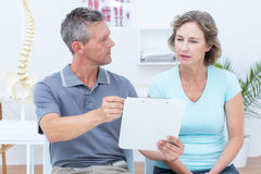 Physiotherapist showing his notes to his patient Royalty Free Stock Images