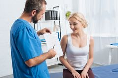 physiotherapist showing human body scheme to woman on massage table