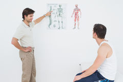 Physiotherapist showing patient something on skeleton chart Stock Photos