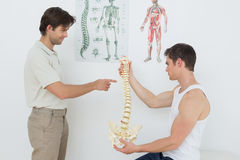 Physiotherapist showing patient something on skeleton model Stock Photography