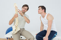 Physiotherapist showing patient something on skeleton model Stock Photo