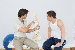 Physiotherapist showing patient something on skeleton model Royalty Free Stock Image