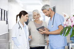 Physiotherapist Showing Reports To Patient And Doctor On Digital. Male physiotherapist showing reports to senior patient and doctor on digital tablet at rehab Royalty Free Stock Photography