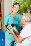 Physiotherapist showing spikey ball. Physiotherapist showing senior men an exercise with a spikey ball Stock Photography