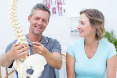 Physiotherapist showing spine model to his patient Royalty Free Stock Image