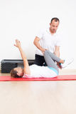 Physiotherapist showing woman an exercise Royalty Free Stock Photography