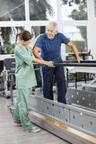 Physiotherapist Standing By Senior Patient Walking Between Paral. Female physiotherapist standing by senior patient walking between parallel bars in fitness Royalty Free Stock Images