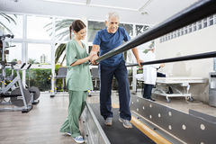 Physiotherapist Standing By Smiling Patient Walking Between Para Royalty Free Stock Photo