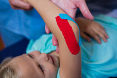 Physiotherapist sticking tape on girl patient Stock Photos