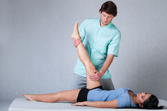 Physiotherapist stretching patient Royalty Free Stock Images