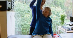 Physiotherapist stretching senior woman shoulder 4k stock video footage